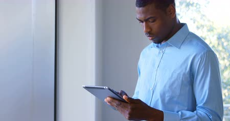 hand on chin : Young black male executive working on digital tablet in modern office. Thoughtful young black male executive looking away 4k Stock Footage