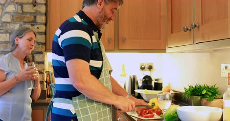 důchodce : Side view of old caucasian senior man cutting vegetable in a kitchen. Old senior woman standing with glass of water and interacting 4k Dostupné videozáznamy