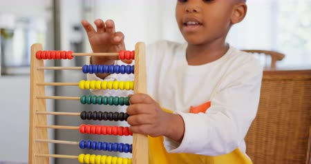 ev gibi : Front view of black boy playing with abacus at comfortable home. Black boy counting the blocks in abacus 4k Stok Video
