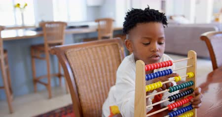 abacus : Front view of black boy playing with abacus at comfortable home. Black boy counting the blocks in abacus 4k Stock Footage