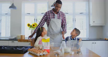 ev gibi : Front view of black father with his children preparing food in kitchen. Black father interacting with his children at home 4k