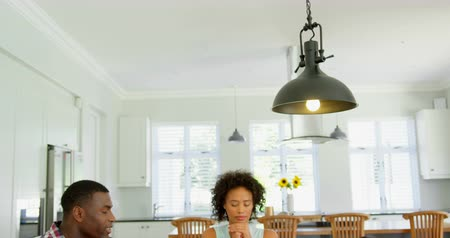 clasped : Black family praying together before having food at home. Black family sitting together on dining table 4k Stock Footage
