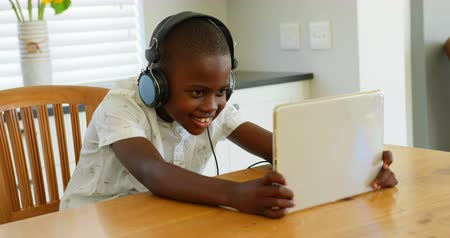 ev gibi : Front view of black boy using digital tablet at home. Black boy playing game on digital tablet 4k Stok Video
