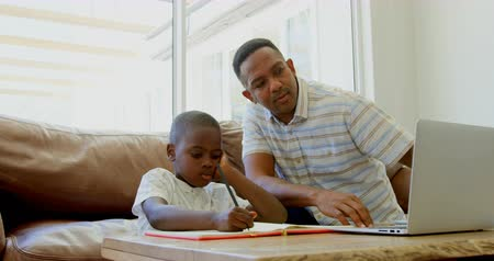 домашнее задание : Front view of black father helping his son with homework at home. Black father using laptop at home 4k