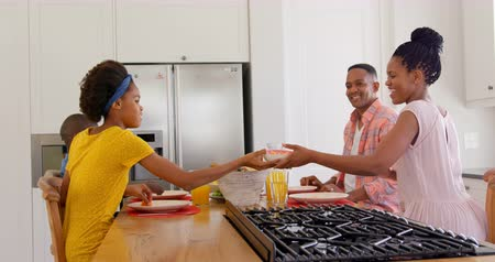 juice jar : Side view of happy black family eating food on dining table at home. Black daughter passing food at dining table 4k