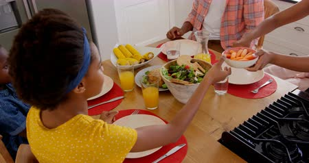 juice jar : High angle view of happy black family eating food on dining table at home. Black mother passing food at dining table 4k Stock Footage