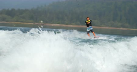 length : Front view of caucasian young man doing tricks on wakeboard in the city river. Rider holding wakeboard rope 4k Stock Footage