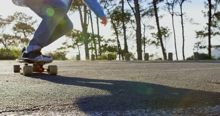gençlik kültürü : Front view of young male skateboarder riding on skateboard on country road. Skateboarder skating on skateboard in the sunshine 4k