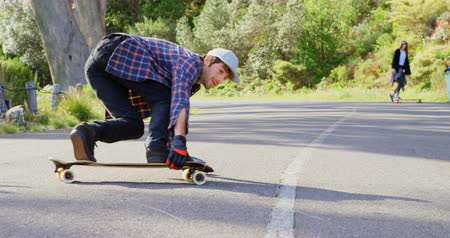 kruvazör : Front view of cool young caucasian man doing skateboard trick on downhill at countryside road. Friends cheering him in background 4k