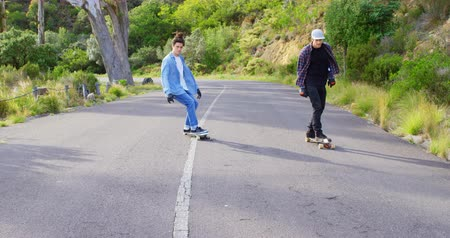 kruvazör : Front view of cool young caucasian skateboarders skating on downhill at countryside road. Skateboarders riding together in the sunshine 4k Stok Video