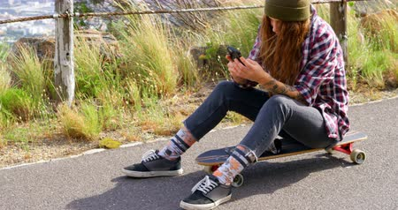 gençlik kültürü : Side view of cool young caucasian blonde woman texting on mobile phone at countryside road. Female skateboarder sitting on skateboard in the sunshine 4k