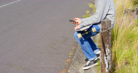 kruvazör : Side view of cool young caucasian man with skateboard using mobile phone at countryside road. Skateboarder sitting on road railing in the sunshine 4k
