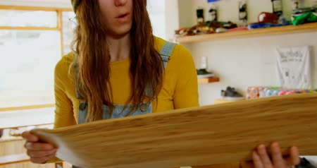 skateboard deck : Front view of young caucasian woman examining skateboard deck in a workshop. Woman working on skateboard deck 4k Stock Footage