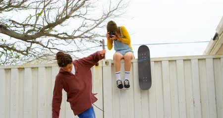 gençlik kültürü : Front view of young caucasian man doing skateboard trick on skateboard ramp at skateboard court. Front view of young caucasian woman sitting on wall and clicking photos with digital camera 4k