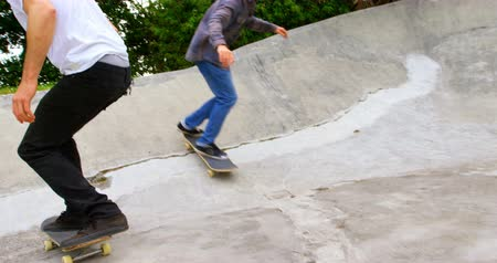 kruvazör : Low section of young men practicing skateboarding on ramp in skateboard park. They are practicing together in the sunshine 4k