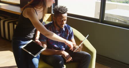görgetés : Front view of young cool mixed-race business team planning and sitting on couch of modern office. They are interacting and discussing over digital tablet 4k