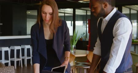 holding document : Side view of young black businessman with laptop using mobile phone in a modern office. Caucasian businesswoman enters and discussing over laptop with businessman 4k