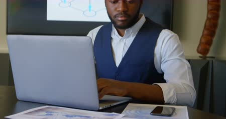 grasduinen : Front view of young black businessman looking at documents while using laptop in a modern office. Documents on the table of conference room 4k