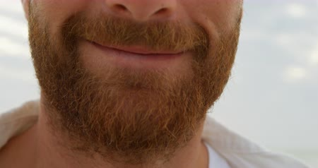 голова и плечи : Close-up young happy caucasian man in beard smiling on the beach. Portrait of smiling man 4k