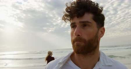 definição : Front view of young caucasian man standing at beach on a sunny day, Woman standing in background and looking at sea 4k