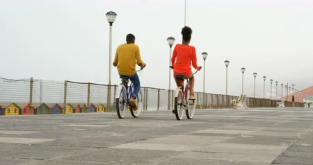 teljes hosszúságú : Rear view of black young couple riding bicycle on promenade at beach on a sunny day. Couple having fun at beach 4k