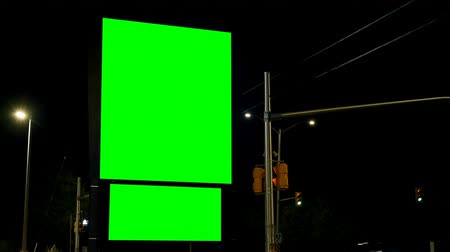 publicidade : Empty billboard with chroma key green screen at night. Traffic light and street lights in the dark 4k