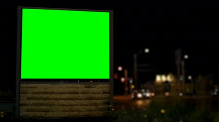 publicity : Empty billboard with chroma key green screen at night. Street lights and moving vehicle in the dark 4k