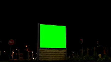 publicidade : Empty billboard with chroma key green screen at night. Street lights and moving vehicle in the dark 4k