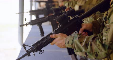 combate : Side view of mixed-race military soldiers shooting rifle in target practice during training. They are pulling the charging handle and aiming 4k