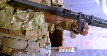 golyó : Mid section of black military soldier loading weapon during military training. He is loading magazine in rifle 4k Stock mozgókép