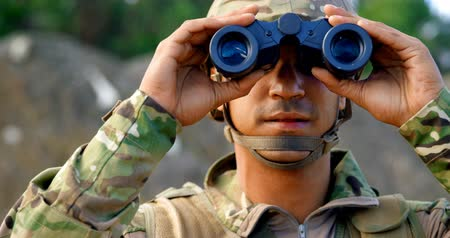 snajper : Front view of young caucasian military soldier observing on field during military training. He is using binocular 4k
