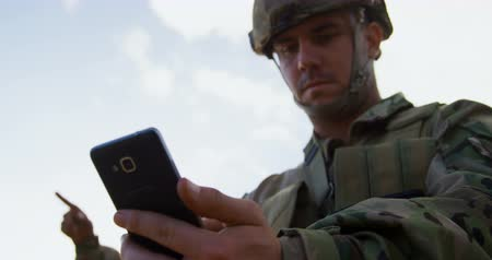 taktika : Low angle view of military soldier using mobile phone during training. Military soldier looking at mobile phone 4k