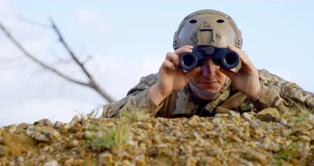armed : Front view of military soldier looking through binoculars during military training. Military soldier lying on the ground 4k