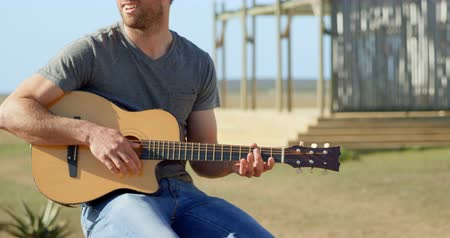 com cordas : Front view of mid-adult caucasian man playing guitar on a sunny day. Man singing and looking away 4k Stock Footage