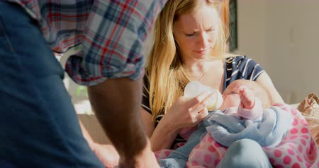 bottle feeding : Mid adult caucasian parents feeding milk her baby from bottle in a comfortable home. Mother holding her baby 4k Stock Footage