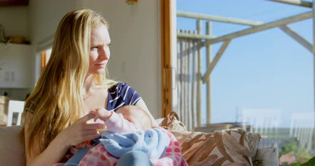 bottle feeding : Front view of mid adult caucasian mother feeding milk her baby from bottle in a comfortable home. Mother looking away 4k Stock Footage