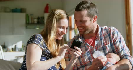bottle feeding : Front view mid adult caucasian parents reviewing photos on mobile phone in a comfortable home. Father feeding milk his baby from bottle 4k Stock Footage