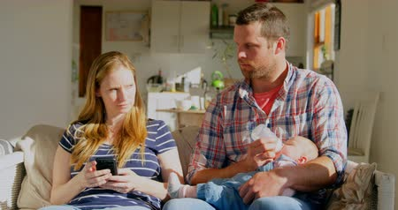 bottle feeding : Front view mid adult caucasian father feeding milk his baby and mother using mobile phone at home. Parents looking each other 4k