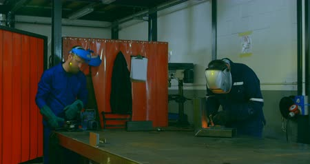 demirci : Time lapse of workers using grinder and welding torch in workshop. Attentive workers working together in workshop 4k