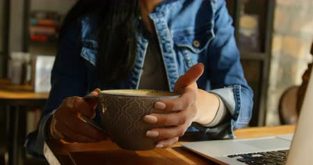 ルーチン : Front view of young Asian woman drinking coffee at table in cafe. Young Asian woman sitting with laptop at table 4k 動画素材