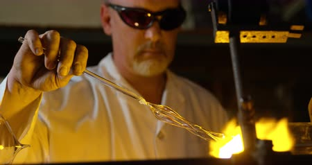 scrutiny : Close-up of mature male worker blowing glass in glass factory. Mature male worker heating glass 4k Stock Footage