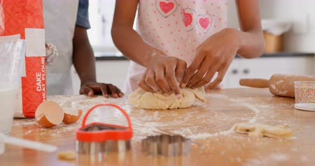 mid section : Mid section of black girl kneading dough on worktop in kitchen at home. Black boy sprinkling flour on dough 4k