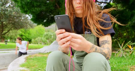 construir : Front view of young caucasian woman listening music on mobile phone in skateboard park. Woman using headphone 4k