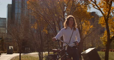 comprimento total : Front view of young Caucasian man walking with bicycle on the street. Carefree man walking along autumn tree in city on sunny day 4k
