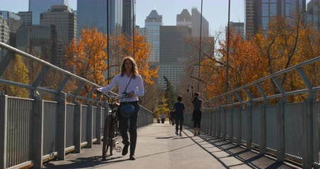 go away : Front view of young Caucasian man walking with bicycle on the bridge. Man walking in the city bridge on a sunny day 4k