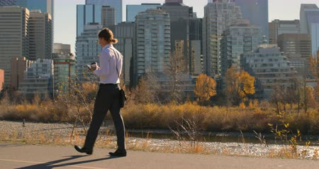 mladistvý : Side view of young Caucasian man using mobile phone while walking on road in city. Modern high-rise buildings on a sunny day 4k