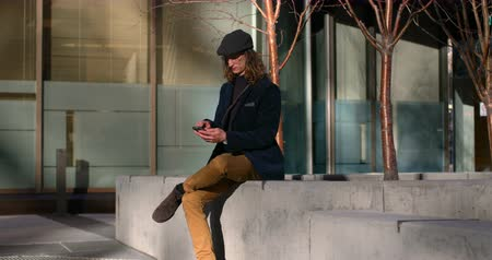 текст : Side view of young Caucasian man using mobile phone in city. Handsome man sitting on surrounding wall 4k