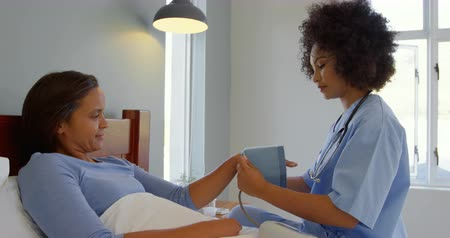 sphygmomanometer : Side view of young mixed-race female doctor checking blood pressure of mature woman at home. She is relaxing on bed 4k