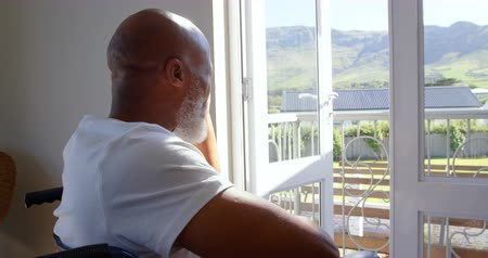 challenged : Side view of mature black handicap man sitting on wheelchair near the window at home. He is thinking and looking through window 4k Stock Footage