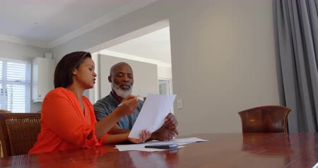 cabeza calva : Front view of mature black couple discussing domestic bills in a comfortable home. They are sitting at dining table 4k